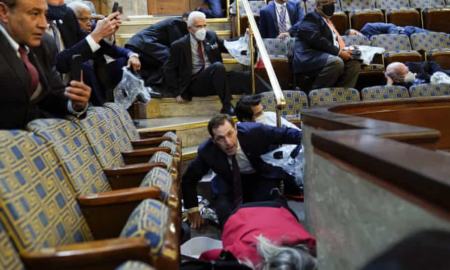 People shelter in the House gallery as rioters try to break into the House Chamber at the Capitol on 6 January. Trump's impeachment trial will be held at the same place the violence unfolded.